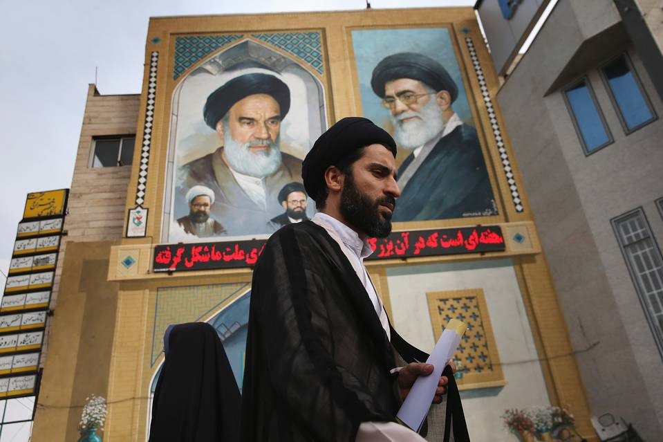 An Islamic Mullah walks past a portrait of the late Ayatollah Khomeini in Qom, Iran.